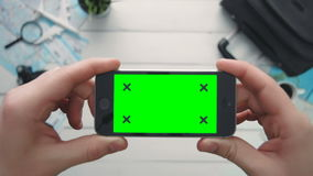 Top view traveler`s hand holding phone horizontal with green screen and tracking points at white wooden desk. Travelling concept. Top view traveler`s hand stock video footage