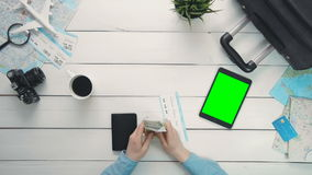 Top view traveler`s hands checking money and ticket and digital tablet with green screen lying at white wooden desk. Travelling concept. Top view traveler`s stock footage