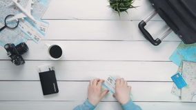 Top view traveler`s hands counting money and checking tickets at white wooden desk stock footage