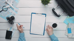 Top view traveler`s hands holding pen and cup of coffee and clipboard with paper at white wooden desk. Travelling concept. Top view traveler`s hands holding pen stock footage
