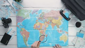 Top view traveler`s hands looking at world map using magnifying glass at white wooden desk. Travelling concept. Top view traveler`s hands looking at world map stock video footage