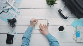 Top view traveler`s hands maing notes in the notebook at white wooden desk stock video footage