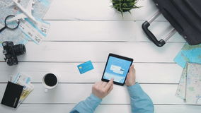 Top view traveler`s hands paying for airplane tickets on line using digital tablet and credit card at white wooden desk. Travelling concept. Top view traveler`s stock footage