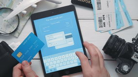 Top view traveler`s hands paying for airplane tickets on line using digital tablet and credit card at white wooden desk