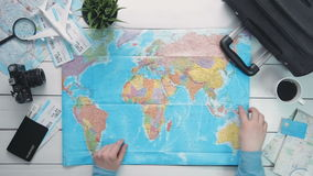 Top view traveler`s hands picking a country for travelling at white wooden desk stock video