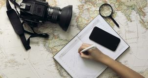 Top view traveler`s hands picking a country for travelling at white wooden desk Travelling concept. Tourist woman looking at world map planning travel adventure stock video footage