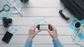Top view traveler`s hands taking a picture of airplance tickets with smart phone at white wooden desk. Travelling concept. Top view traveler`s hands taking a stock video footage