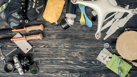 Top view of traveling items on wooden background. Packing for active vacations. Journey preparation. Copy space royalty free stock images