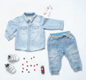 Top view trendy denim look of baby boy clothes with toy and snea Royalty Free Stock Image