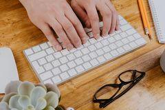 Top View of trendy wooden Office Desk with keyboard, white earphones and office supplies, working mans hands.  royalty free stock photos