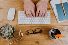 Top View of trendy wooden Office Desk with keyboard, white earphones and office supplies, working mans hands.  stock photos