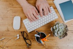 Top View of trendy wooden Office Desk with keyboard, white earphones and office supplies, working mans hands royalty free stock photos