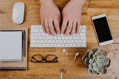 Top View of trendy wooden Office Desk with keyboard, white earphones and office supplies, working mans hands.  stock photography