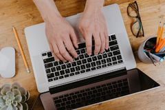 Top View of trendy wooden Office Desk with keyboard, white earphones and office supplies, working mans hands.  stock images