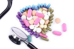 TOP VIEW OF TRIANGLE SHAPED PILLS WITH STETHOSCOPE. Top view of pills shaped in a heart with a stethoscope and assorted pills, capsules and tablets inside royalty free stock photos