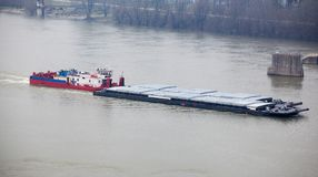 Tugboat Pushing a Heavy Barge. Top view of Tugboat pushing a heavy barge on the river Stock Photo
