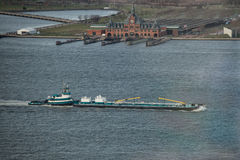 Top view of Tugboat pushing a heavy barge on the river Stock Images