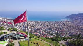 Top view of Turkish flags on mountain on background of city and sea. Clip. Turkish resort town located in mountainous. Area on beach stock video
