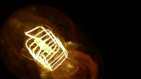 Top of view of turn on and turn off in slow motion with dust, retro vintage light bulb with old technology with filament built-in stock video