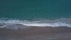 Top view turquoise waves break on empty pebble beach. Pure sea from bird`s eye. Aerial top view turquoise waves break on empty pebble beach. Pure calm sea from stock video