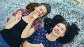 Top view of two beautiful girls in headphones listening music dancing and smiling while lying on bed stock video