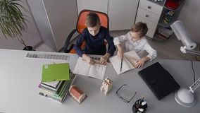 Top view. The two brothers sit at the desk at home in white room and draw drawings. The children finished doing homework. And fun slapped each other in the palm stock video