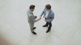 Top view of two businessmen discussing financial report then tell goodbye shaking hands and walking away in lobby of. Business center indoors stock video footage