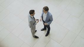 Top view of two businessmen greeting and shaking hands and chatting during coffee break in lobby of business center. Indoors stock footage