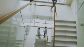 Top view of two businessmen meet at staircase in modern office center and talking while female colleagues walking stairs stock video