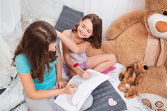 Top view of two cheerful charming sisters sitting and colouring. In playroom at home Stock Photos