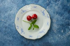 Top view of two cherries on a blue and white porcelain plate. Blue background stock photography