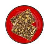 Cocoa honey peanut granola bars on red plate Royalty Free Stock Photos