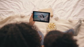 Top view of two girlfriends sitting on bed at home talking on skype on tablet computer with their friend having vacation stock video footage