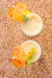 Top view two glasses with pineapple cocktail on a sandy beach cl stock photo