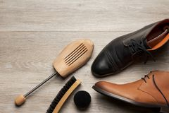 Diagonal composition of shoes and a shoe tree. Top view of two leather men`s shoe and boot with a shoe tree and a brush, room for text royalty free stock photo