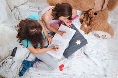 Top view of two lovely sisters sitting and colouring together. In children room Stock Photos