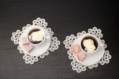 Top view of two mugs of coffee with ice cream on a saucer with Turkish Delight. Lacy napkins, black table Stock Image