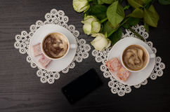 Top view . Two mugs of coffee with milk, Turkish delight on a saucer, telephone white roses. Stock Photography