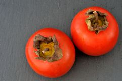 Top view of two persimmons on a slate plate Stock Photo