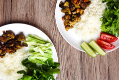Top view of two plates with healthy lunch. White rice, thai fried meat and vegetables. FLat lay on wooden background Stock Photos