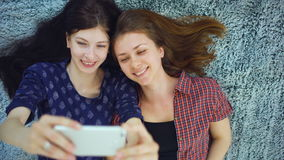 Top view of two pretty girls in pajamas making selfie portrait on bed in bedroom at home stock footage