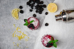 A top view of two refreshing cocktails with blackberries and green mint on a gray background. Organic and natural stock photos