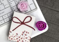 Top view of two roses and white laptop on background. stock photos