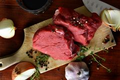 Fresh raw beefsteak on the wooden cutting board, top view stock photos