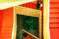 Top view of two young people with their mobile devices on the staircase inside of the building - Image stock photo