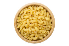 Top view of uncooked macaroni pasta in wooden bowl isolated Stock Image