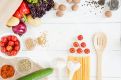 Top view of uncooked pasta with tomatoes and fresh raw vegetables. On wooden table Stock Image