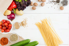 Top view of uncooked spaghetti and fresh raw vegetables and spices. On wooden table Stock Photos