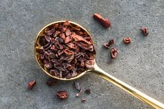 Cocoa Nibs on a Gold Spoon. Top view of unprocessed cocao nibs on a gold spoon stock images