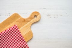 Top view of unused brand new brown handmade wooden cutting board and red napkins on white wooden table background - Food and kitch Stock Photos